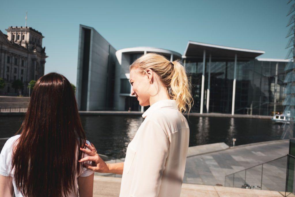 Zwei junge Frauen mit Blick Richtung Zukunft. Die eine hält ihre Hand unterstützend auf die Schulter der anderen.